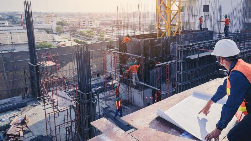 Ein Mann mit Schutzhelm und Warnweste kniet auf dem Dach eines Neubaus. Er betrachtet das geschehen auf der Baustelle während er vor sich einen großen Plan ausbreitet.