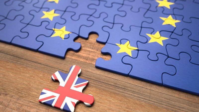 Ein Puzzle mit einer Europaflagge liegt auf einem Tisch. Ein Teil ist entfernt und zeigt die Flagge des Vereinigten Königreichs.