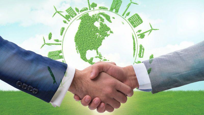 Zwei Personen in gepflegten Anzügen schütteln sich die Hände. Im Hintergrund schwebt der Umriss des Globus umgeben von Windkraftanlagen, Autos, Häusern und Bäumen - alle sind aus  grünem pflanzlichen Material geformt.