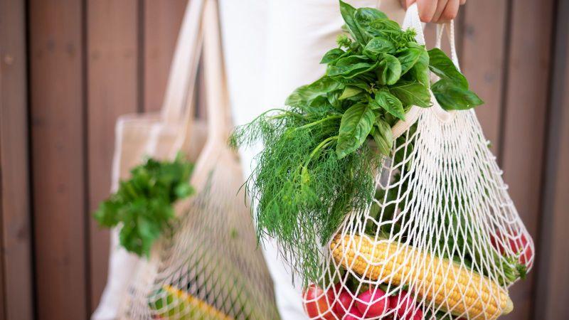Eine weiß gekleidete Frau trägt beidseitig zwei Einkaufsnetze mit verschiedenem frischen Gemüse. Sie steht vor einer Wand aus dunkelbraunen Holz.