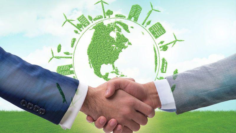 Zwei Personen in Anzügen schütteln sich die Hände. Im Hintergrund schwebt der Umriss des Globus umgeben von grünen Windkraftanlagen, Autos, Häusern und Bäumen.