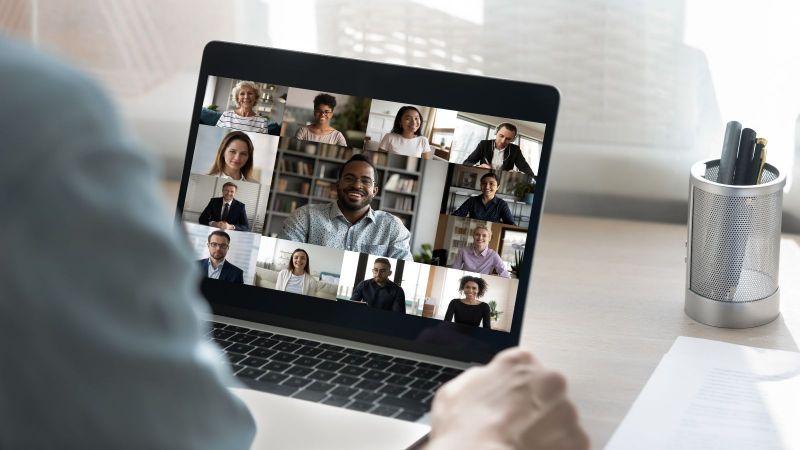 Ein Zuhöhrer sietzt vor einem Laptop mit einem Online-Meeting.