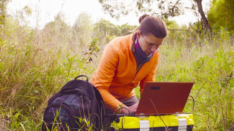 Eine Frau in Trekking-Garderobe  hockt im hohen Grass.  Neben ihr liegt befindet sich ein Rucksack. Vor ihr steht ein aufgeklappter Laptop auf einer großen Plastikkiste.