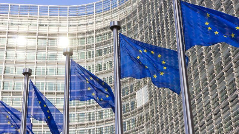Bild des EU Kommissions Gebäude in  Brüssel mit Europa Fahnen im Vordergrund