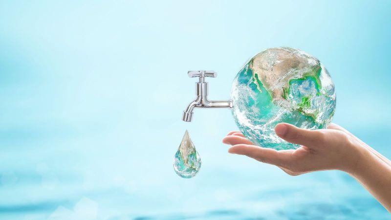 In einer abstrackten Bildinstallation wird die Erdkugel von zwei Händen hochgehalten. Aus der kleinen Erdkugel ragt ein tropfender Wasserhahn. Der Hintergrund ist gefüllt mit Wasser.
