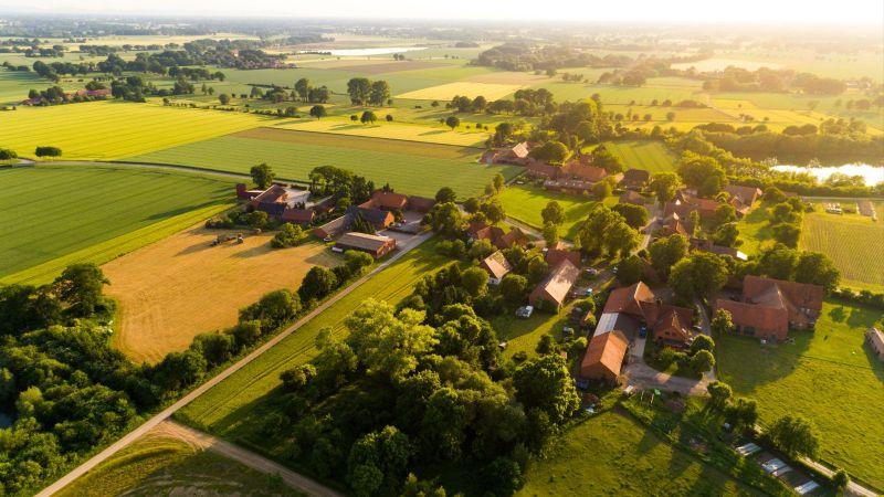 Eine weiträumiger Bauernhof steht inmitten einiger Baumgruppen. Um das Gehöft erstrecken landwirtschaftrliche Flächen über flaches Land bis zum Horizont.