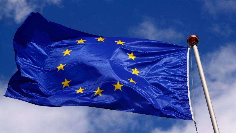 Eine Flagge der EU weht am Fahnenmast vor blauem Himmel mit weißen Wolken.