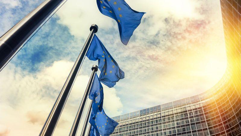 Flaggen der EU wehen vor dem EU-Gebäude während des Sonnenuntergangs.