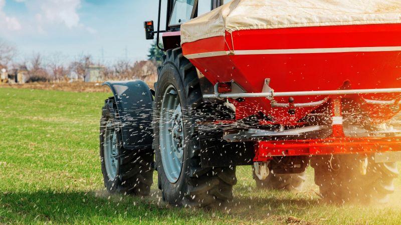 Ein Tracktor verteilt Düngemittel mithilfe seines angekoppelten Schleuderstreuers auf einer stoppeligen Rasenfläche.