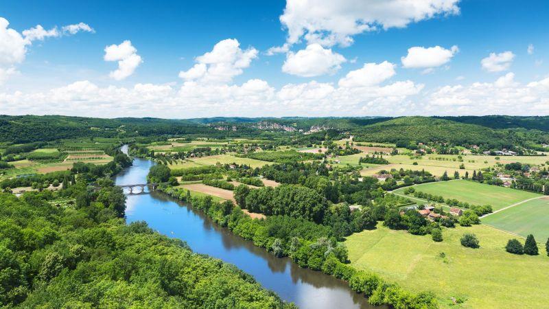 Panoramablick auf das Tal der Dordogne in Frankreich. Ein Fluss fließt durch eine Landschaft mit Feldern, Wäldern und kleineren Dörfern.