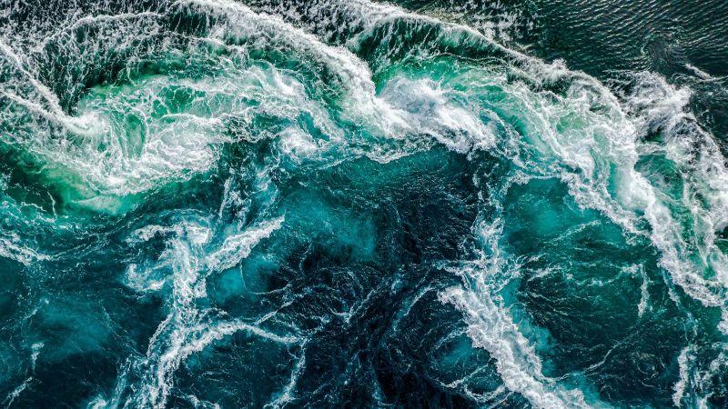 Aus der Vogelperspektive fällt der Blick auf das dunkelblaue Wasser eines aufgewühlten Meeres. Die Gischt bildet ein weißes Muster auf der Wasseroberfläche.