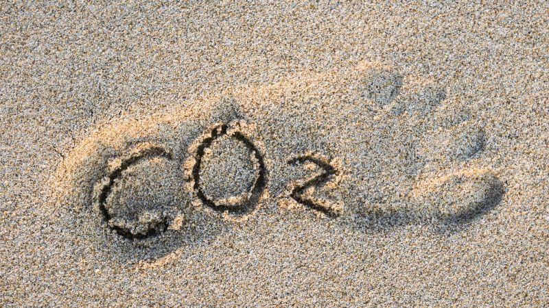 CO2-Text im Umriss eines Fußes in goldenem Sand.