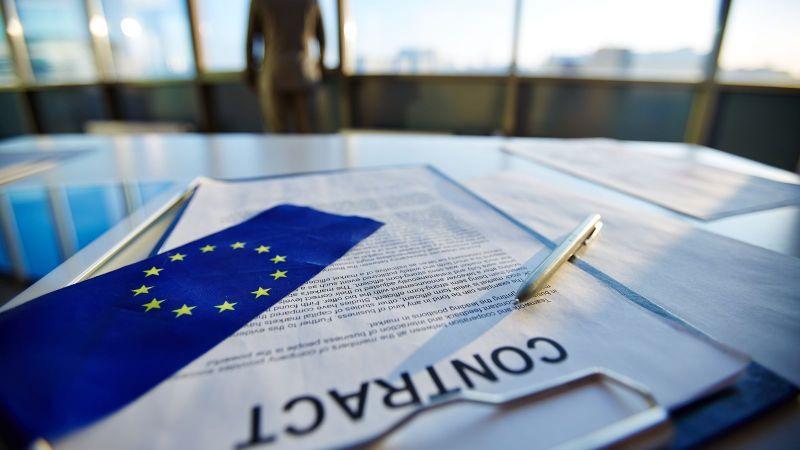 Ein Vertrag liegt auf einem Tisch. Auf dem Vertrag liegen ein Stift und eine EU-Flagge.