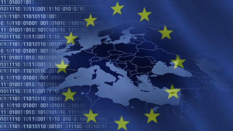Durch eine transparente Fahne der Europäischen Union fällt der Blick auf binäre Zahlenreihen, welche sich horizontal bis in eine Karte der europäischen Mitgliedsstaaten erstrecken.