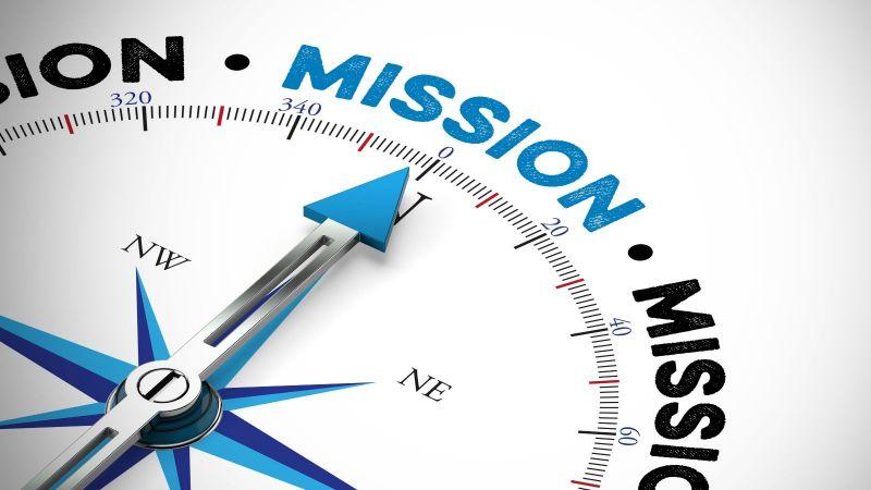 Eine blau-schwarze Kompassnadel auf weißem Untergrund zeigt auf das blaugeschriebene Wort Mission.