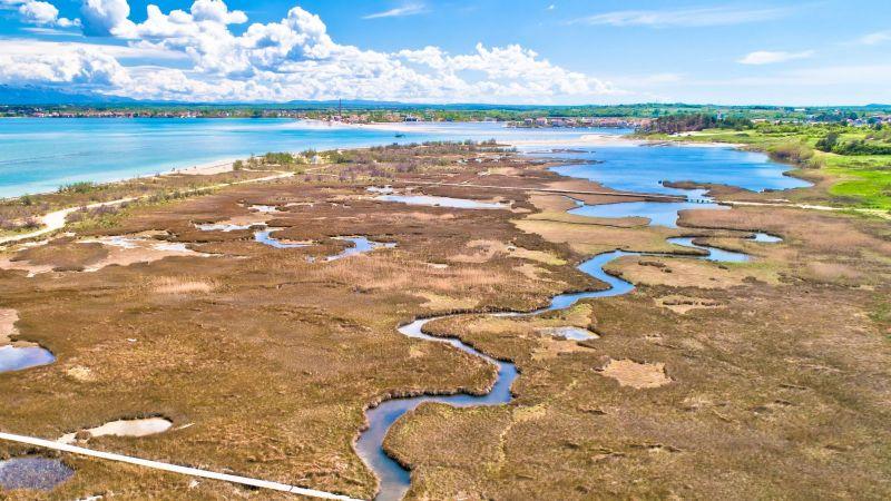 Ein Fluss schlängelt sich durch Marschland auf das Meer zu. Im Delta liegt eine Gemeinde.