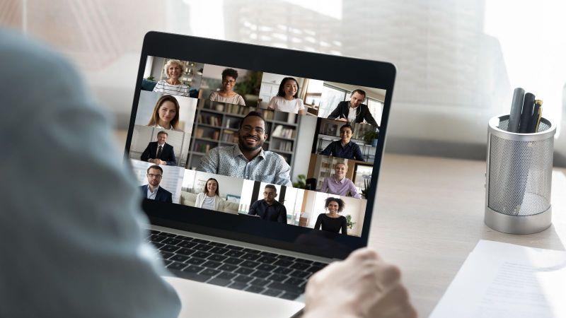 Ein Zuhörer sitzt vor einem Laptop mit einem Online-Meeting.