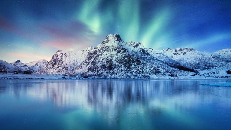 Vor einem stillen Wasser steht ein schneebedeckter Berg. Dahinter sind Nordlichter zu sehen.
