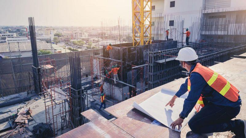 Ein Bauarbeiter mit weißen Helm kniet auf einer Betonoberfläche und überblickt den Bau eines großen Gebäudes. Das Gebäude ist unfertig.