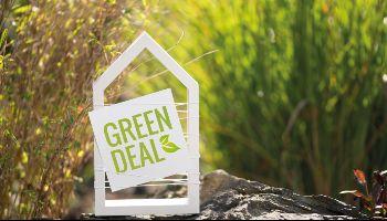 Ein weißer Rahmen in Form eines Hauses steht auf einem Stein mit Pflanzen im Hintergrund. Eine weiße Karte mit der grünen Aufschrift