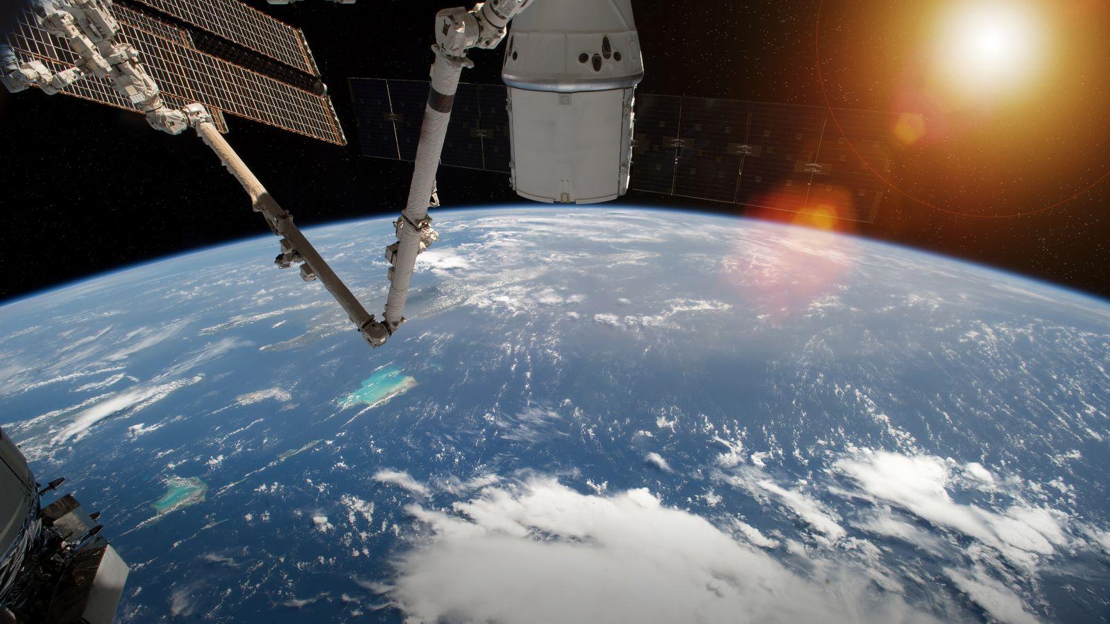 Blick auf die Erdkugel aus dem Weltall. Am Rand des Bildes sind Teile einer Raumstation und die Sonne über der Erde zu sehen.