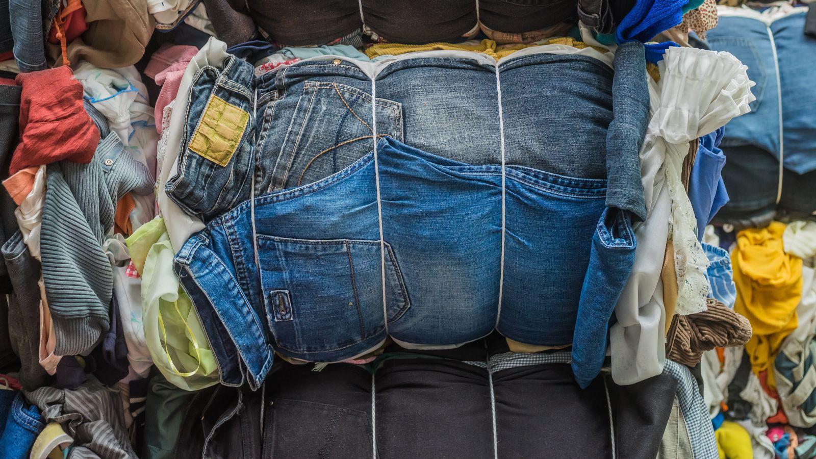 Alttextilien sind zusammengebunden zu Bündeln. Im Vordergrund stehen Jeans.