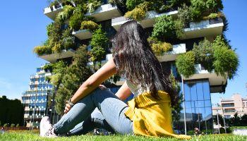 Eine Frau sitzt auf dem Rasen vor einem begrünten Hochhaus.