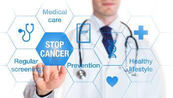 Ein Arzt steht hinter einer durchsichtigen Wand mit medizinischen Symbolen. Er drückt mit dem Zeigefinger auf das Symbol Stop Cancer.