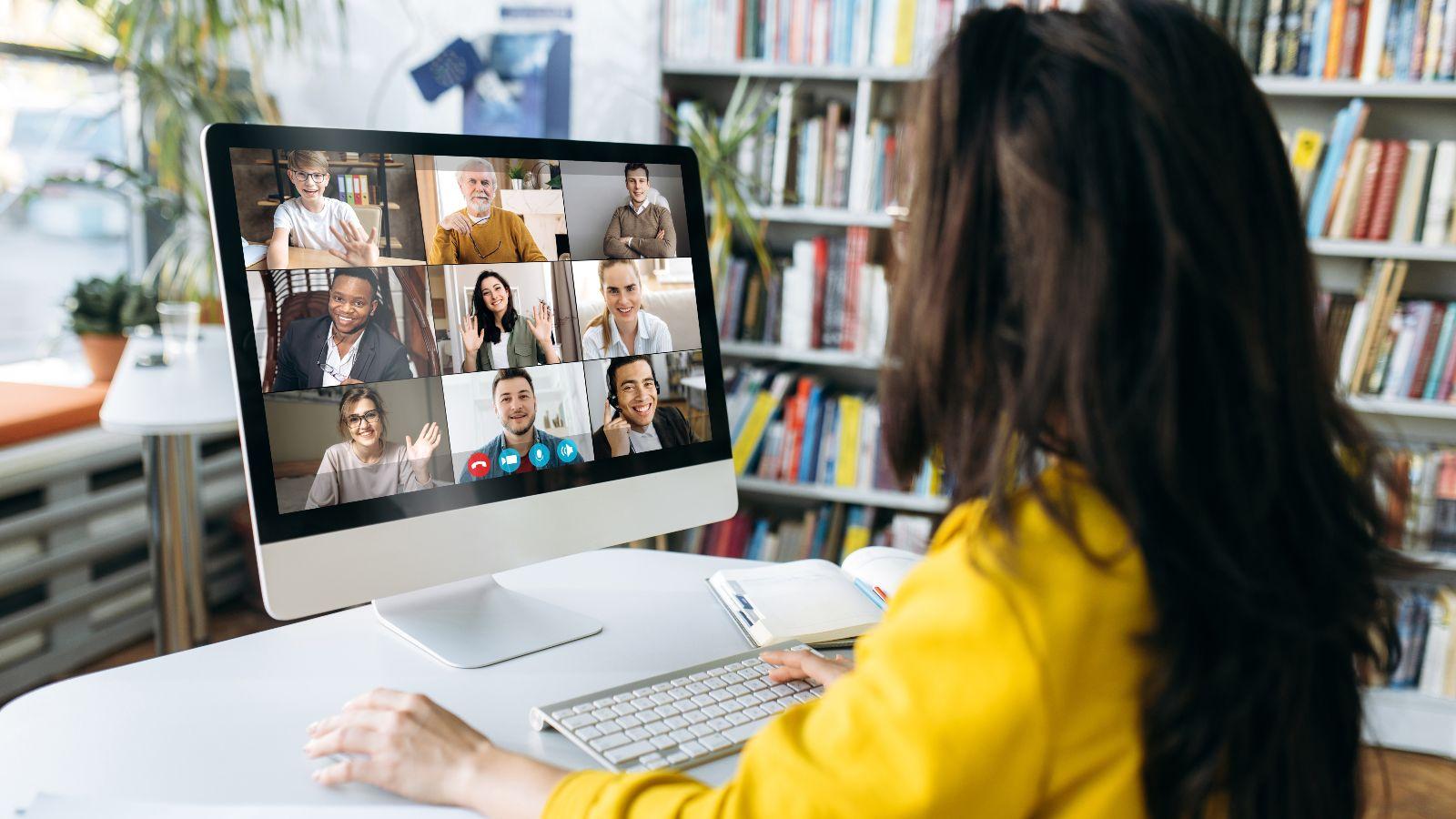 Eine Zuhörerin sitzt vor einem Bildschirm, auf dem mehrere Teilnehmer/innen einer Online-Konferenz zu sehen sind.
