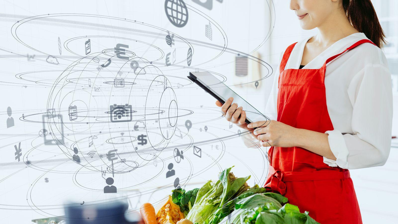 Eine Frau mit einer roten Schürze steht in der Küche und hält ein Tablet. Vor ihr liegt frisches Gemüse. Im Raum schweben diverse illustrierte Piktogramm um eine skizzierte Kugel.