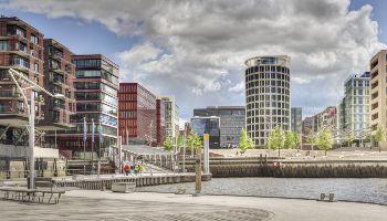 Der Blick fällt auf eine moderne Stadt über ein Wasser mit Bänken am gestalteten Ufer.
