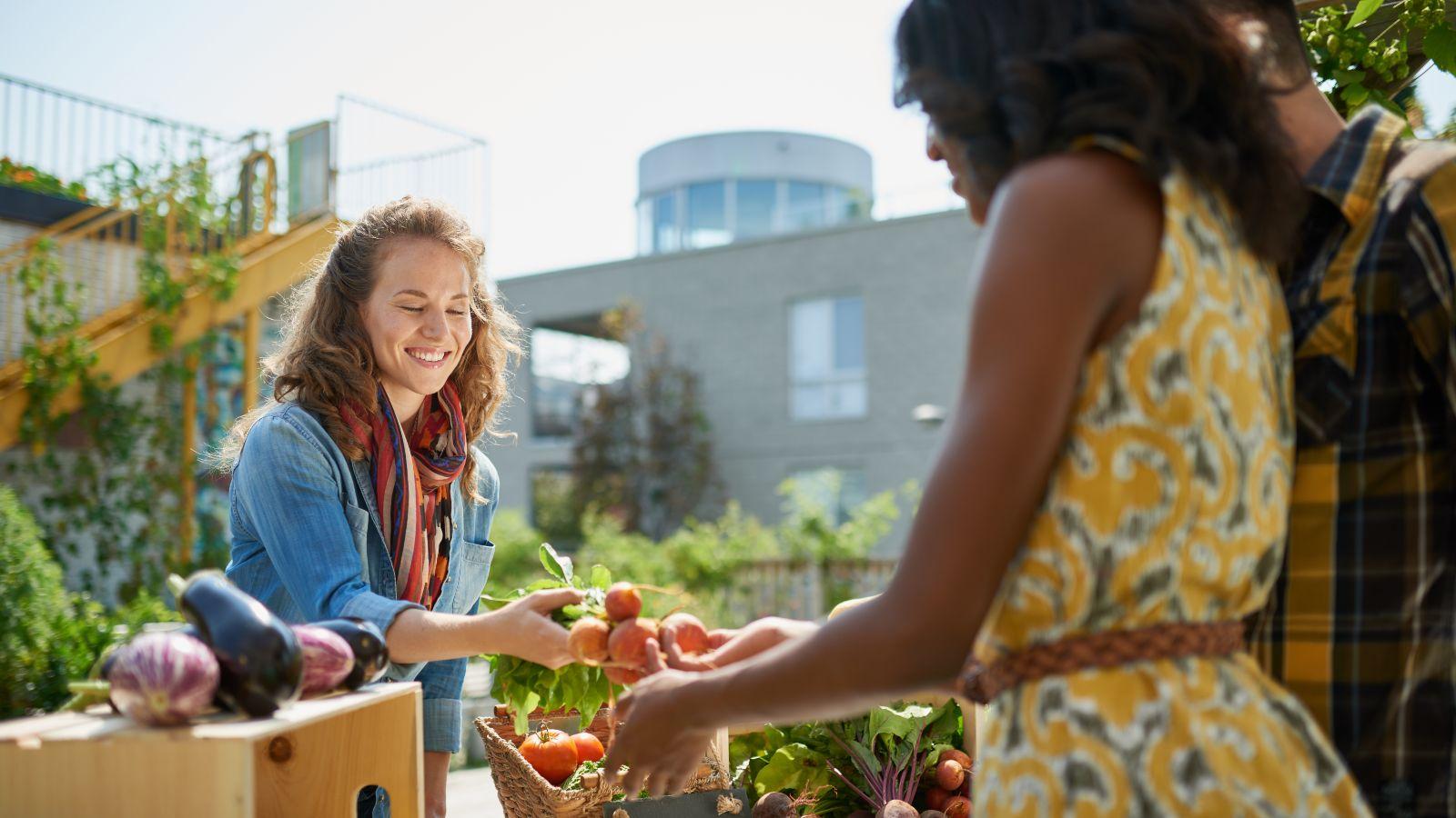 Eine Frau verkauft Gemüse an einem Stand in einem Dachgarten.