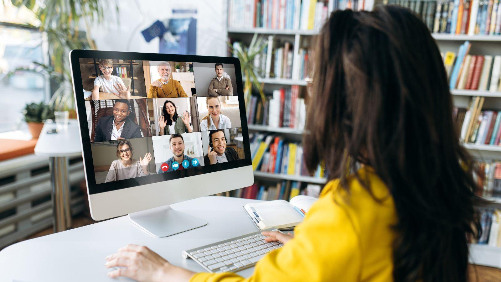 Eine Zuhörerin sitzt vor einem Bildschirm, auf dem mehrere Teilnehmende einer Online-Konferenz zu sehen sind.