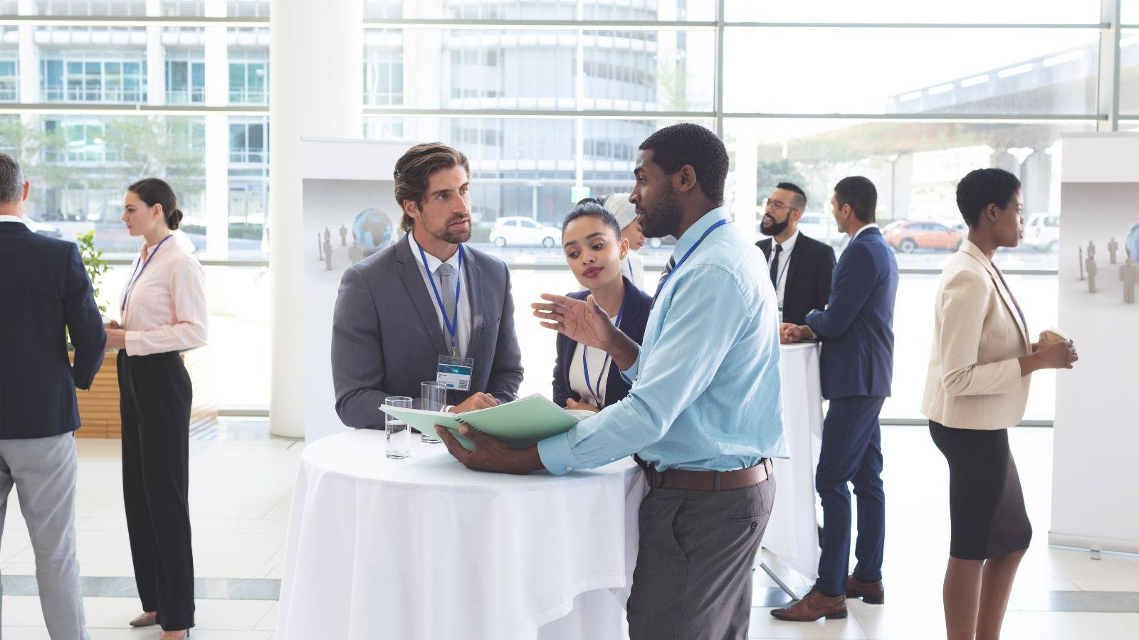 Gruppen von zwei oder drei Personen stehen in einem verglasten Raum und unterhalten sich.