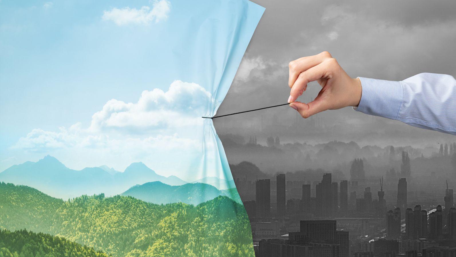 Eine Hand zieht einen Vorhang mit blauem Himmel, Wolken und grünen Hügeln über eine düstere Industrielandschaft. Der Vorhang bedeckt die Hälfte des Bildes.