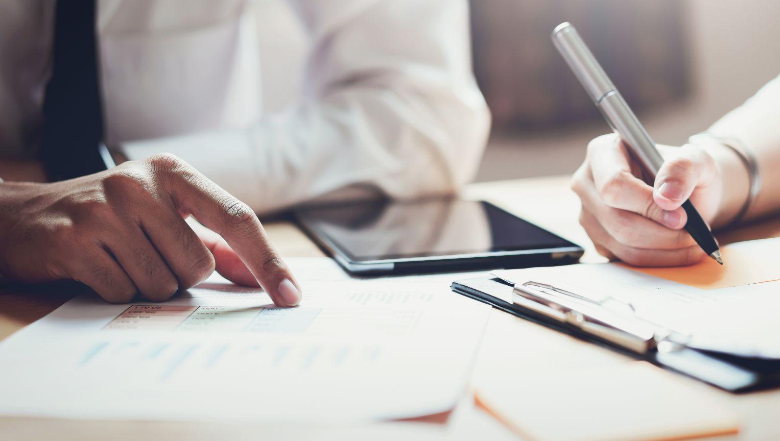 Zu sehen ist ein Schreibtisch und die Arme und der Oberkörper von zwei Personen. Eine Person hält einen Stift und schreibt auf einem Blatt Papier, die andere Person zeigt auf einem weiteren Papier auf etwas.