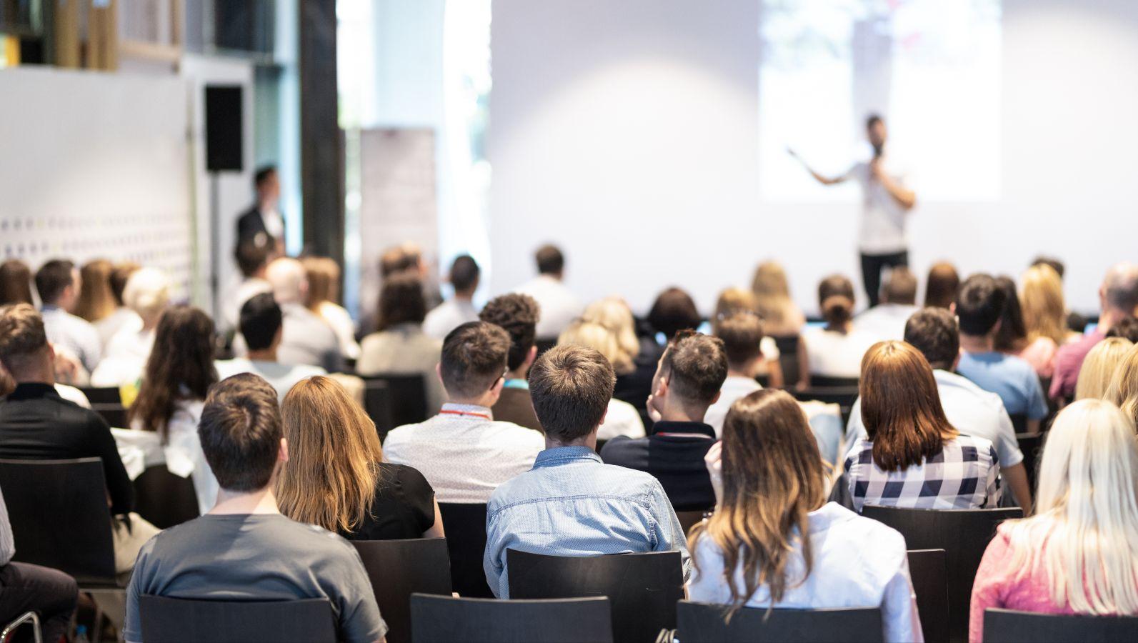 Bild eines Konferenzvortrages mit Blick auf den Sprecher auf dem Podium.