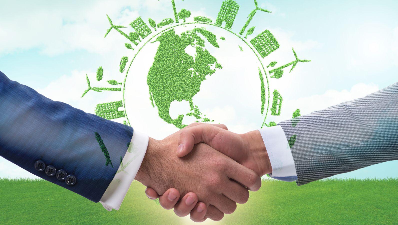 Zwei sich schüttelnde Hände von zwei Geschäftsleuten im Vordergrund. Im Hintergrund eine grüne Weltkugel mit grünen Symbolen von Energie, Windrktaft usw.