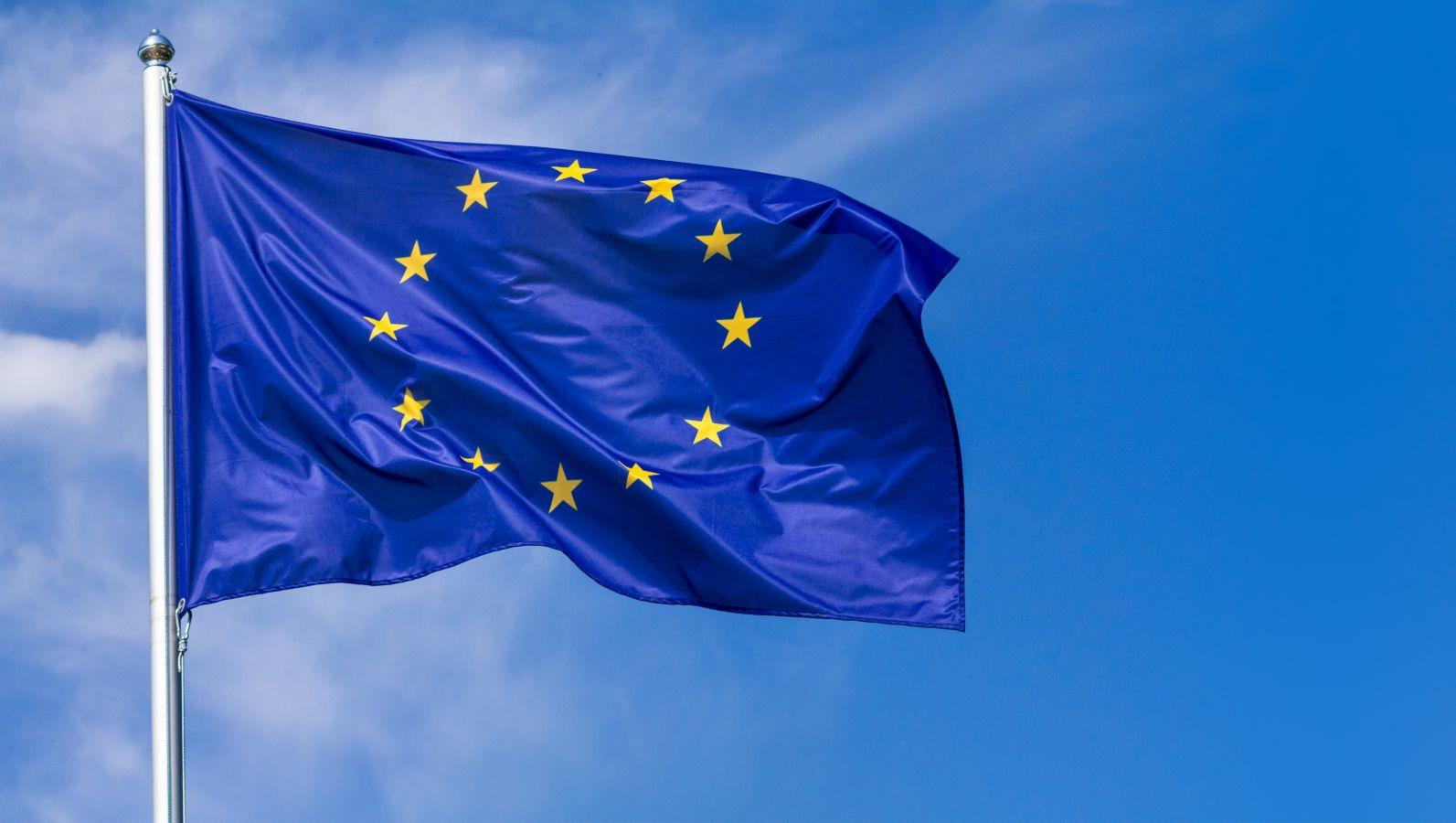 An dem Obertteil eines Fahnenmastes weht die Flagge der Europäischen Union vor blauem Himmel.