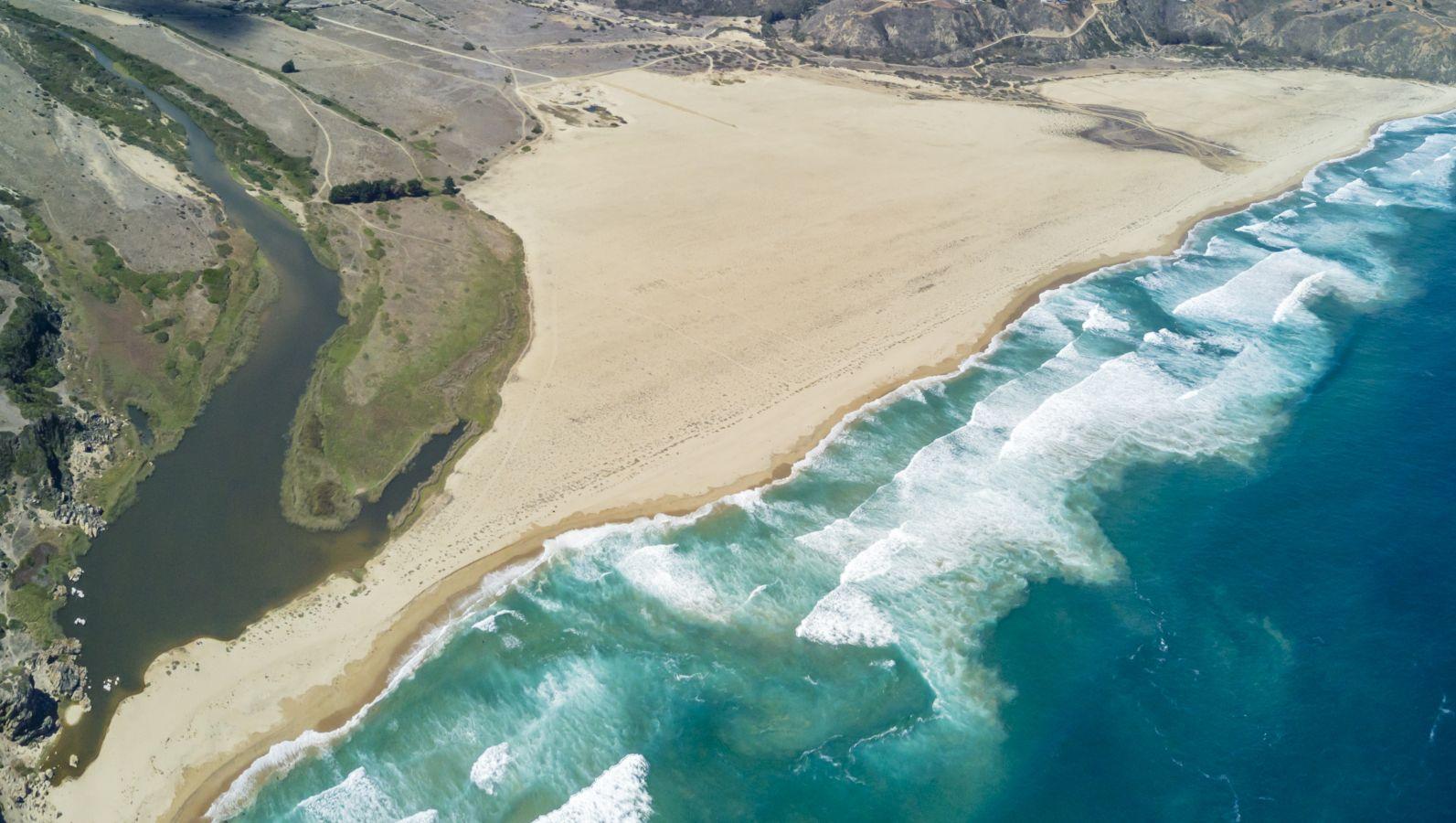 Sandiges Festland trifft an einer Küste auf türkis-blaues Meer. Große Wellen brechen in der Brandung kurz vor dem Strand.