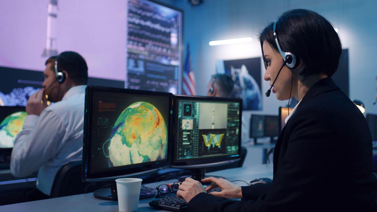 Eine Frau im Anzug und Headset sitzt vor einem Monitor auf dem die Erde vom Weltall aus betrachtet zu sehen ist. Im Hintergrund sitzt ein Mann vor einem Bildschirm.