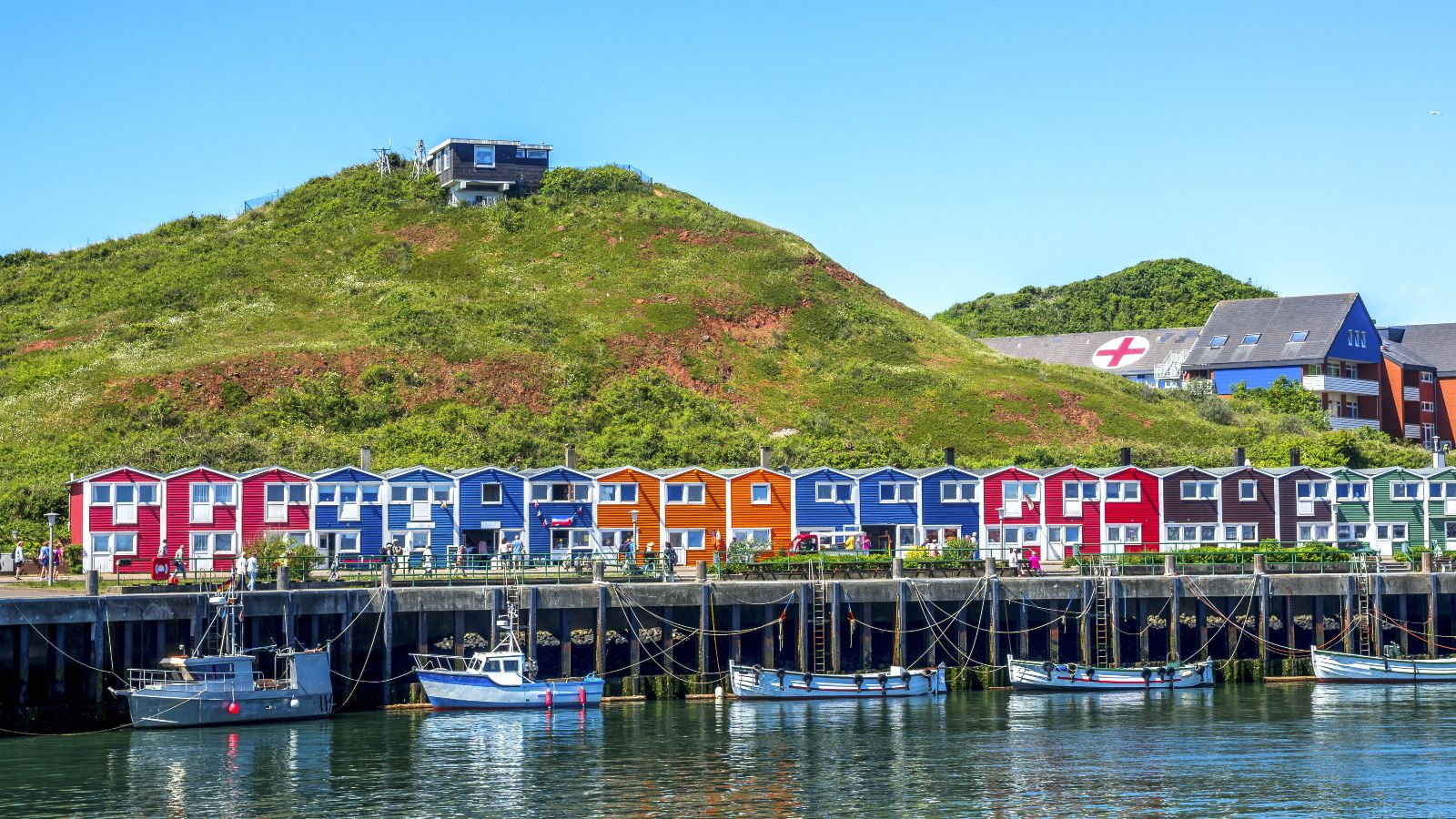 Vom Meer aus ist eine Reihe bunter Fischerhäuser zu sehen. Davor liegen Boote vor Anker.