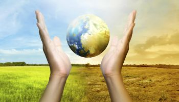 The globe floats between two hands. Its left side shows a healthy earth with a green meadow landscape in the background. The right side shows a desert planet in front of a dried-up soil landscape.