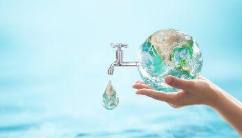 In einer abstrackten Bildinstallation wird die Erdekugel von zwei Händen hochgehalten. Aus der kleinen Erdkugel ragt ein tropfender Wasserhahn. Der Hintergrund ist gefüllt mit Wasser.