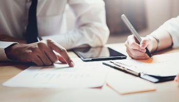 Ein Mann und eine Frau sitzen zusammen geschäftig an einem Tisch. Der Mann deutet auf eine Tabelle, während die Frau Notizen schreibt.