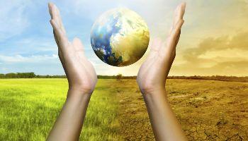 Zwischen zwei Händen schwebt die Erdkugel. Ihre linke Seite zeigt eine gesunde Erde mit einer grünen Wiesenlandschaft im Hintergrund. Die rechte Seite zeigt einen Wüstenplaneten vor einer ausgetrockneten Bodenlandschaft.