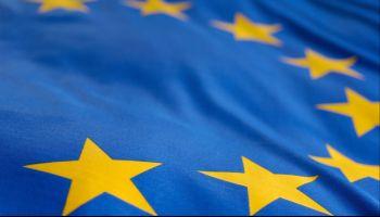 Im Wind weht die Flagge der Europäischen Union: Auf dem blauen Untergrund liegt ein Kreis aus zwölf goldenen fünfzackigen Sternen.